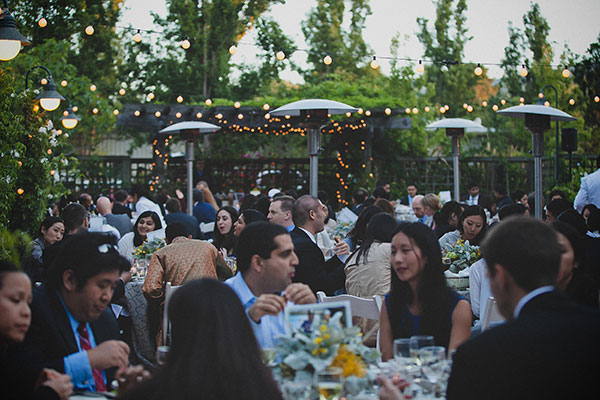 Wedding guests enjoying dinner at an outdoor wedding reception in Los Altos by destination wedding planner, Mango Muse Events