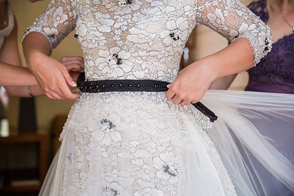 Bride getting dressed in her white and black lace wedding gown for a Calistoga destination wedding by Destination wedding planner, Mango Muse Events