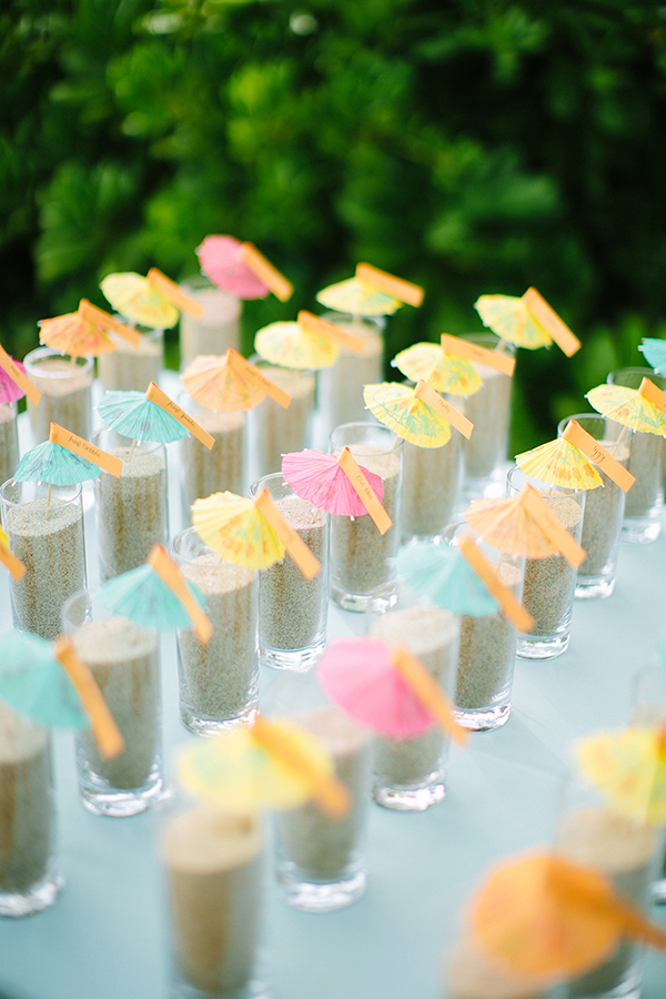 Cocktail umbrella seating cards in sand for a Hawaii destination wedding by destination wedding planner, Mango Muse Events