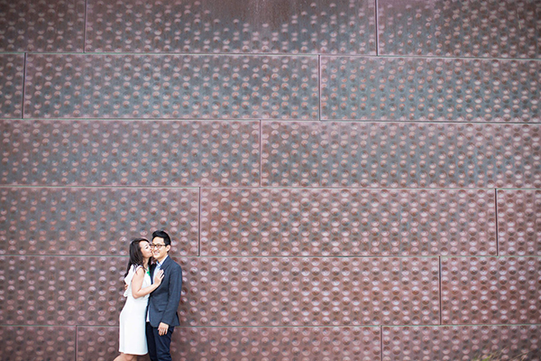 An engaged couple taking photos at their engagement session with their photographer at the De Young Museum in San Francisco