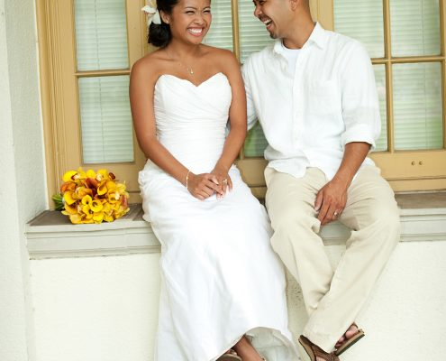A bride and groom laughing as they sit and relax at their Hawaii destination wedding planned by Destination wedding planner, Mango Muse Events