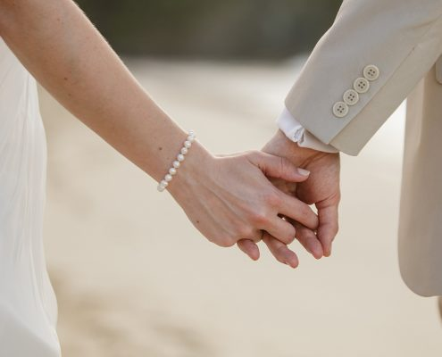 Bride and groom holding hands on the beach at their Caribbean destination wedding by Destination wedding planner, Mango Muse Events