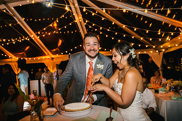 Bride and groom happily cutting into their wedding pie at their Hawaii destination wedding by Destination wedding planner, Mango Muse Events