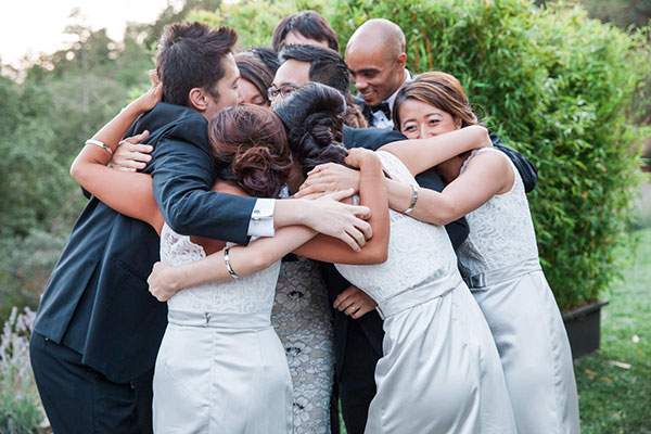 Wedding party in a group hug at a Calistoga destination wedding by Destination wedding planner, Mango Muse Events