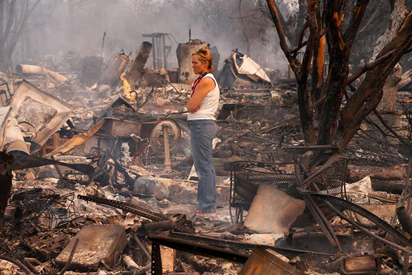A woman staring at the destruction of the wine country firestorm