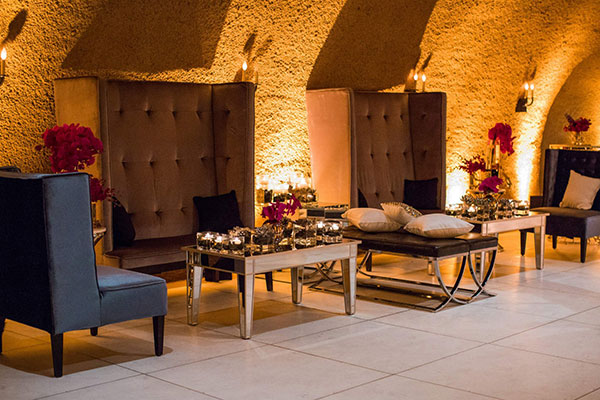 Lounge space with sofas and chairs at a Calistoga Ranch wine cave wedding reception by Destination wedding planner, Mango Muse Events