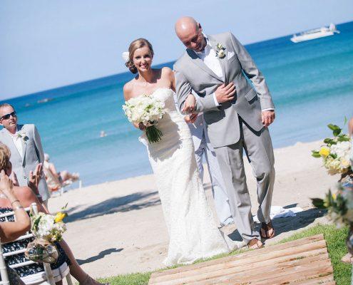 Bride and groom walking down the aisle at a beachside Big Island Hawaii destination wedding by Destination wedding planner Mango Muse Events