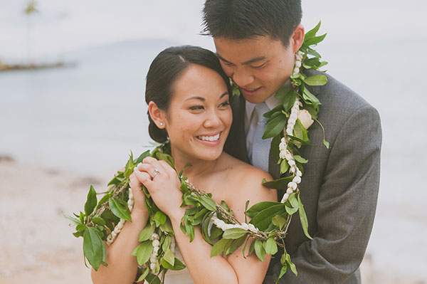 Bride and groom with a Hawaiian maile pikake lei at their Hawaii wedding by Destination wedding planner, Mango Muse Events