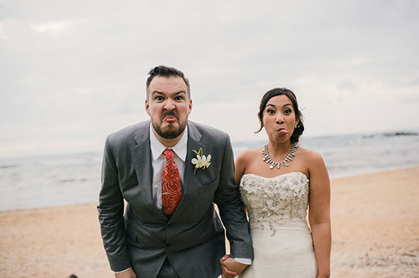 Bride and groom sticking out their tongues and making funny faces at their Hawaii destination wedding by Destination wedding planner Mango Muse Events