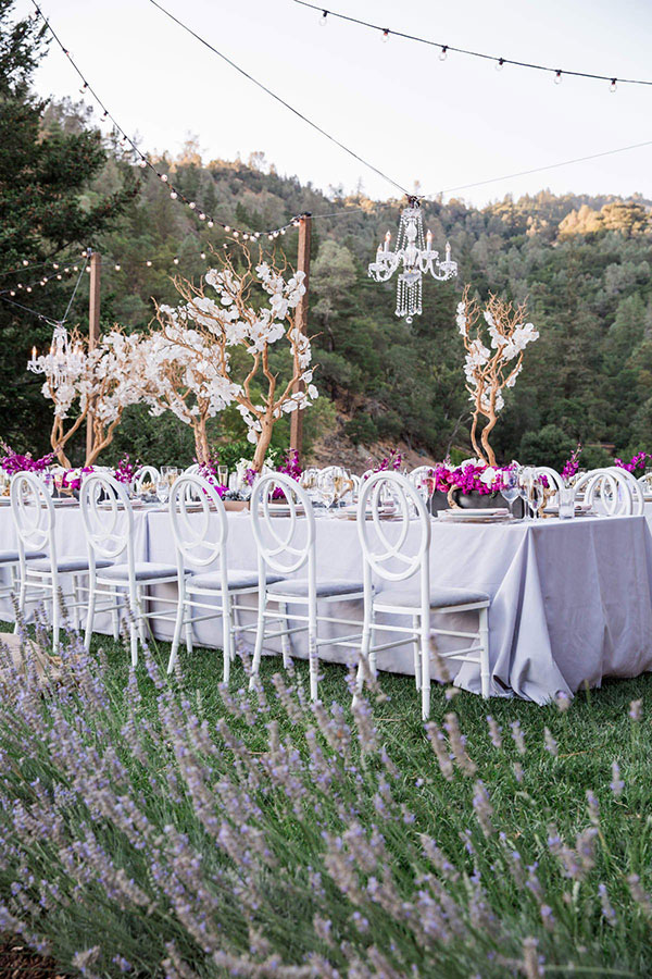 Elegant chandeliers and string lights as wedding lighting for a Calistoga Ranch wedding by Destination wedding planner Mango Muse Events