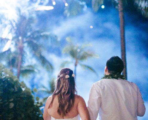 Bride and groom enjoying fireworks at a Hawaii destination wedding by Destination wedding planner Mango Muse Events