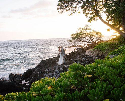 A sunset kiss on the rocks at a Big Island Hawaii destination wedding by Destination wedding planner Mango Muse Events