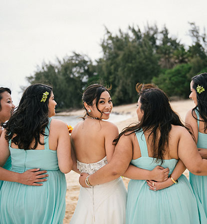 Bride and bridesmaids together at a Hawaii beach wedding by Destination wedding planner, Mango Muse Events