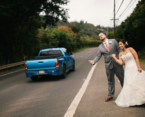 Bride and groom pretend hitch hiking at their Hawaii destination wedding by Destination wedding planner Mango Muse Events