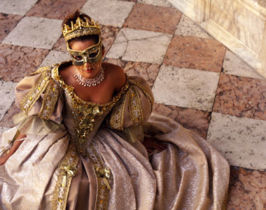 Woman in ball gown and gold mask as Mardi Gras wedding inspiration by Destination wedding planner, Mango Muse Events