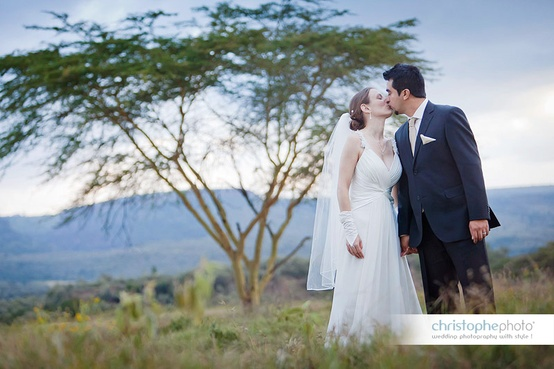 Wedding couple kissing next to a yellow acacia tree at a Kenya destination wedding shared by Destination wedding planner, Mango Muse Events