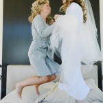 Bride and bridesmaid jumping on a bed before a wedding shared by Destination wedding planner Mango Muse Events