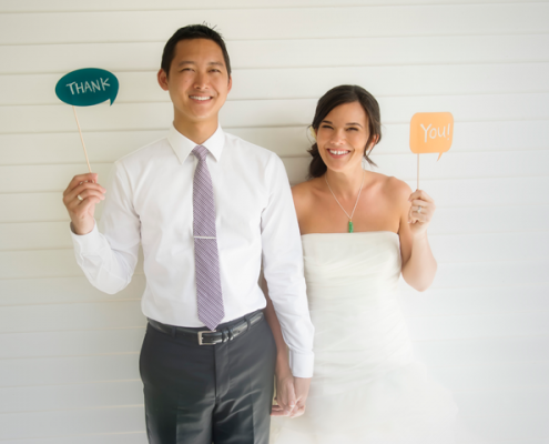 Wedding couple holding thank you signs for their thank you notes