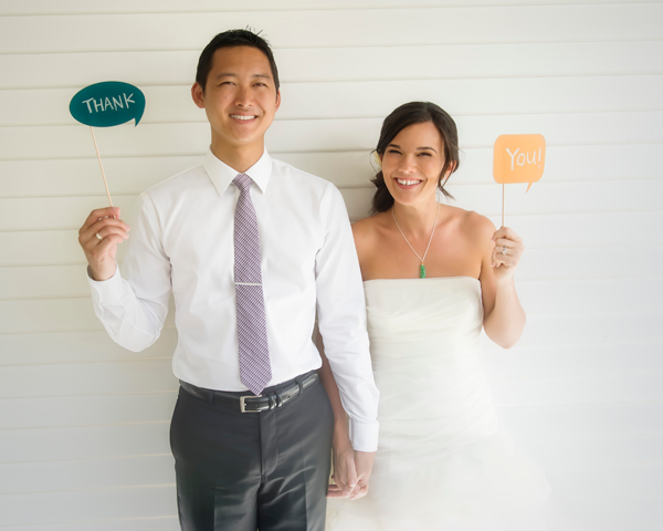 Wedding couple holding thank you signs for their thank you notes for a Hawaii destination wedding by Destination wedding planner Mango Muse Events