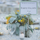 Wedding table design with real candles in tall votives, yellow green and gray floral centerpieces and travel table names by Destination wedding planner Mango Muse Events