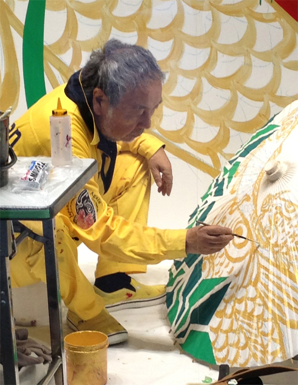Artist painting an umbrella in Kyoto Japan design inspiration by Destination wedding planner Mango Muse Events