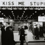 Photo of a couple kissing beneath an marquee reading Kiss me Stupid