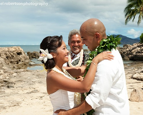 Wedding officiate and newlyweds at destination wedding in Hawaii by destination wedding planner Jamie Chang of Mango Muse Events.