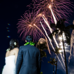 Couple stands outside watching fireworks after their destination wedding reception in Hawaii. Event design by destination wedding planner Jamie Chang of Mango Muse Events.