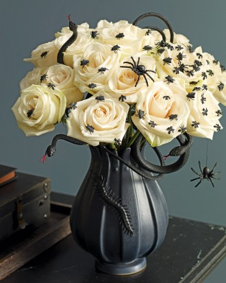 Fake spiders crawling on floral centerpiece for Halloween.