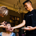 Groom feeding bride Jamie Chang destination wedding planner of Mango Muse Events while she gets ready for the wedding.