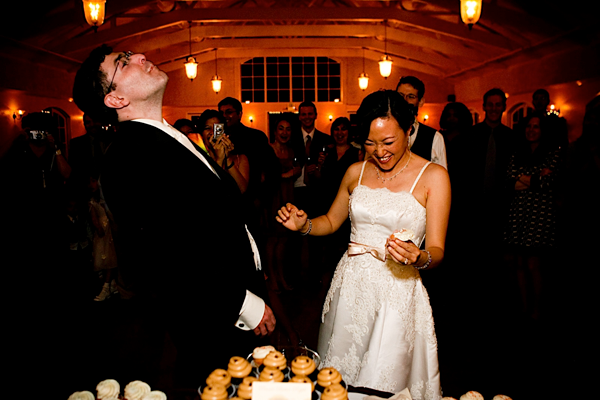 Bride and groom laughing, eating their wedding cake. Event design by Jamie Chang destination wedding planner of Mango Muse Events.