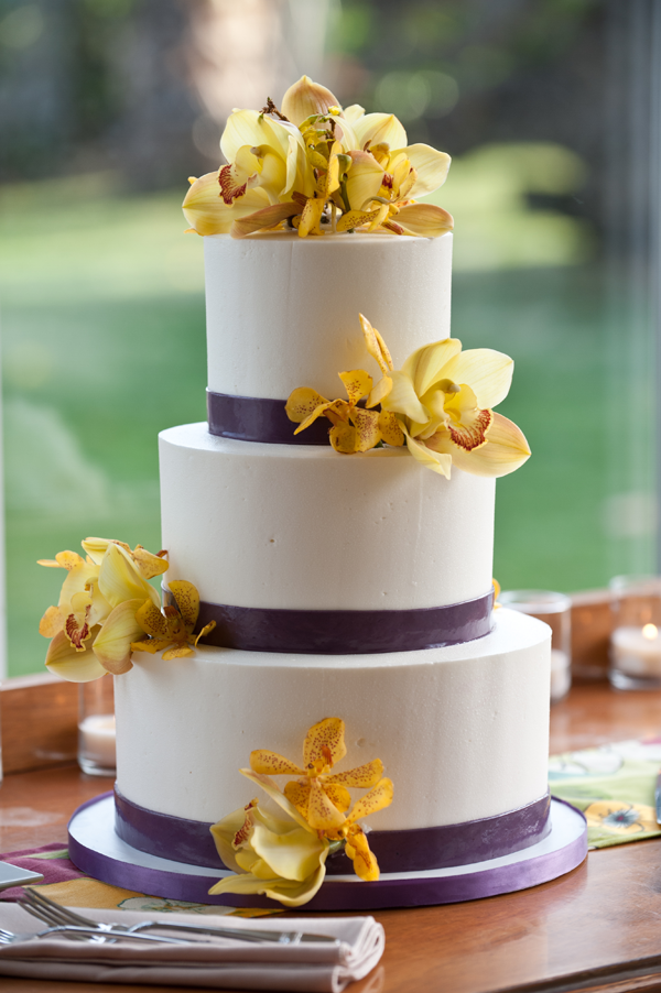 Wedding cake with yellow orchids at a destination wedding in Hawaii by Jamie Chang destination wedding planner of Mango Muse Events.