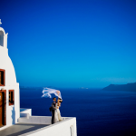 Couple outside of church at their destination wedding in Santorini, Greece.