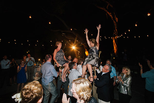 Mother of the bride and mother of the groom having a ball during the Hora dance at a Hawaii destination wedding on the Big Island by destination wedding planner Mango Muse Events