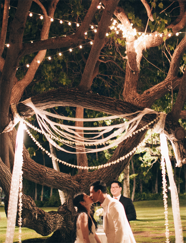 Bride and groom at a nighttime ceremony for a Hawaii destination wedding at Lanikuhonua by Destination wedding planner, Mango Muse Events