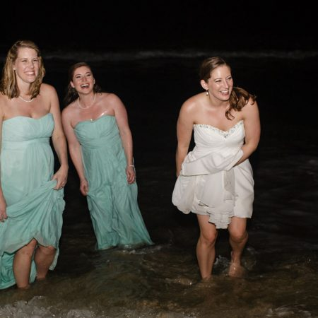 Bride and bridesmaids in the ocean at a Caribbean destination wedding by Destination wedding planner Mango Muse Events