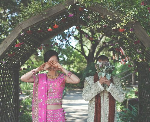 Bride and groom under a decorated arch at their multicultural wedding by Destination wedding planner Mango Muse Events
