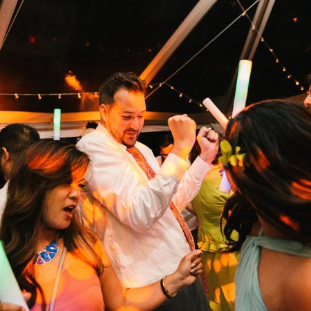 Guest and groom dancing all night long at a Hawaii destination wedding by Destination wedding planner Mango Muse Events