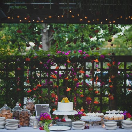 Wedding cake and dessert bar with garland backdrop at a multicultural wedding by Destination wedding planner Mango Muse Events