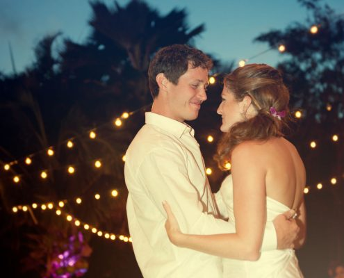 First dance under string lights at a Hawaii destination wedding by Destination wedding planner Mango Muse Events