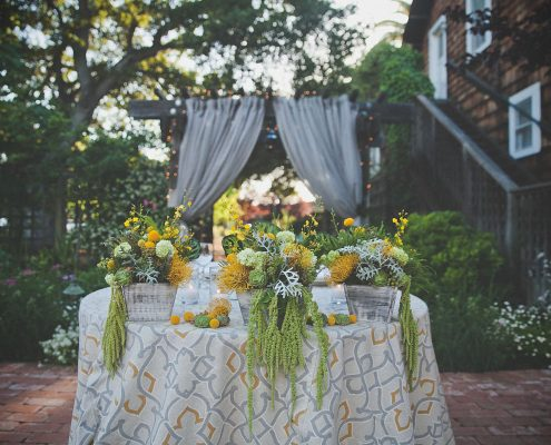 Green and yellow floral centerpieces for a sweetheart table by Destination wedding planner Mango Muse Events