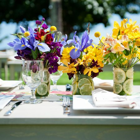 Purple and yellow flower centerpieces at a Hawaii destination wedding by Destination wedding planner Mango Muse Events