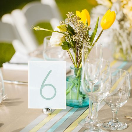 Ribbon runners and yellow flower centerpiece at a Hawaii destination wedding by Destination wedding planner Mango Muse Events