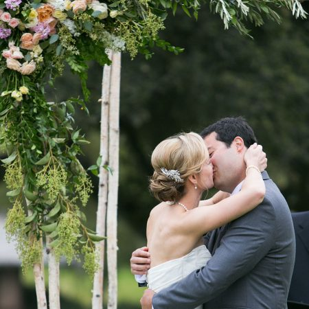 Bride and groom kiss at their wedding ceremony at a Carmel destination wedding by Destination wedding planner Mango Muse Events