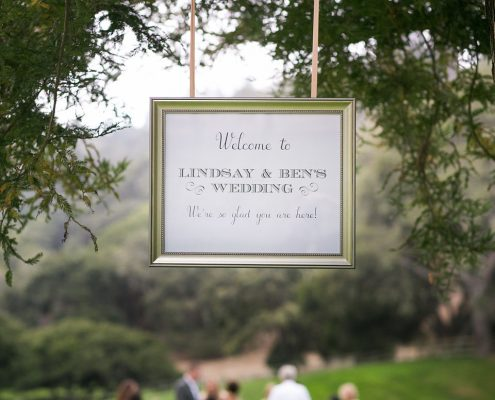 Welcome sign hung from a tree at a Carmel destination wedding by Destination wedding planner Mango Muse Events