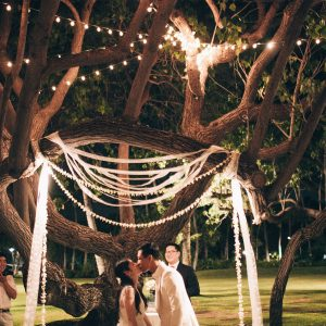 Bride and groom at their non-traditional nighttime ceremony at a Hawaii destination wedding at Lanikuhonua private estate by Destination wedding planner, Mango Muse Events