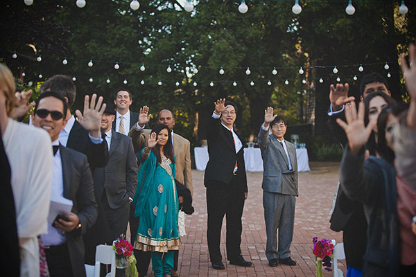 Wedding guests raising their hands towards the couple at a Hindu Chinese wedding ceremony planned by Destination wedding planner, Mango Muse Events