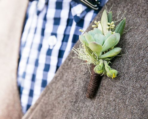Succulent boutonniere on a groomsmen vest at a destination wedding by destination wedding planner Mango Muse Events