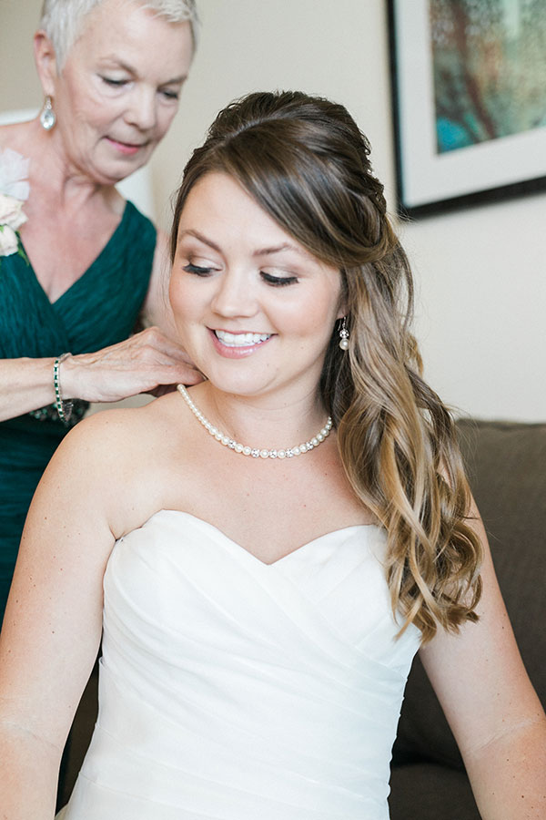 Mother of the bride helping her daughter get dressed at this Hawaii destination wedding planned by Destination wedding planner, Mango Muse Events