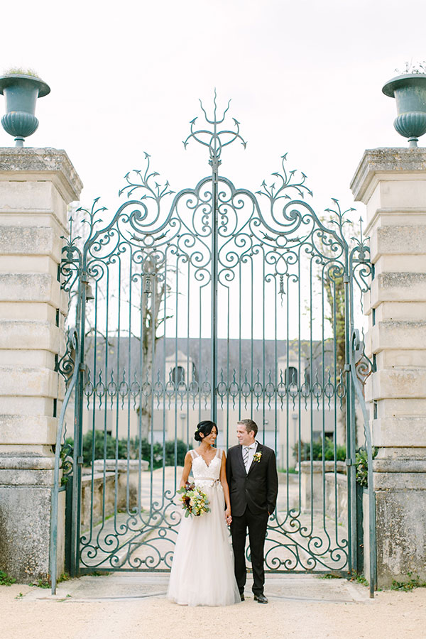 Bride and groom in front of elegant green gates at their French Chateau wedding in Loire Valley France by destination wedding planner Mango Muse Events